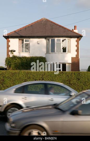 cars driving past a detached suburban house Preston Lancashire England UK causing noise pollution disturbance - Stock Image