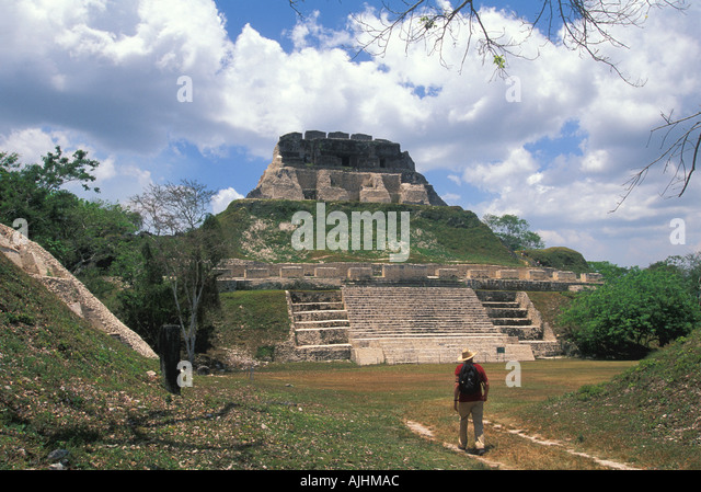 Belize Central America Xunantunich Maya Ruins lone hiker walking toward main temple pyramid - Stock Image