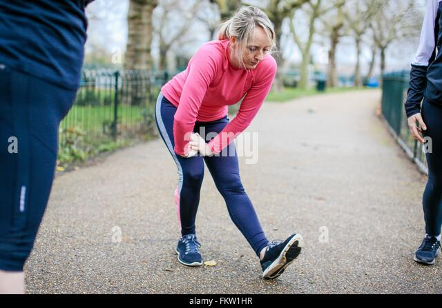 Women and teenage girl doing preparation warm up in park - Stock Image