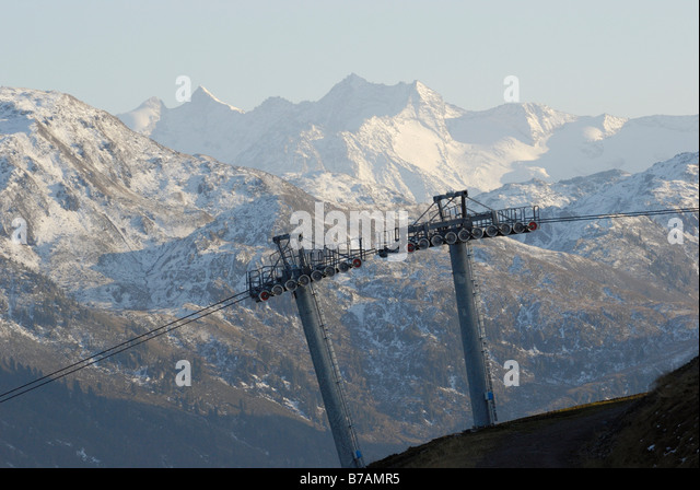 Supporting poles with the ropes of a cable car, in front of snow-covered mountains, Schatzberg, Grimmler Tauern - Stock Image