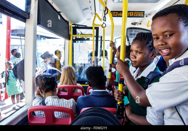 Cape Town South Africa African MyCiTi bus public transportation Black boy student school uniform riding home girl - Stock Image
