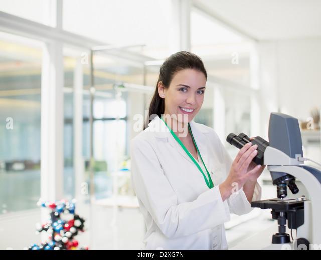 Portrait of confident scientist using microscope in laboratory - Stock Image