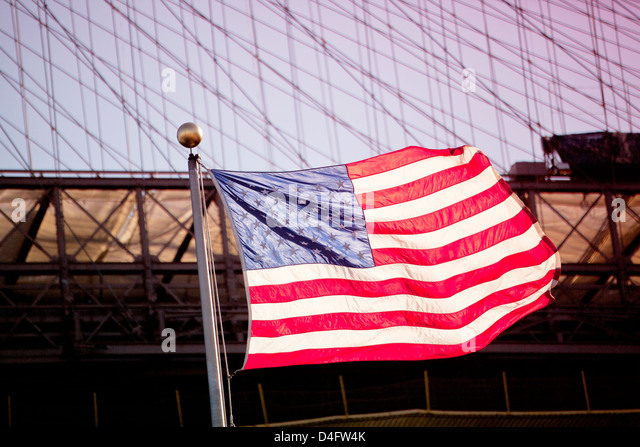 American flag waving by urban bridge - Stock Image