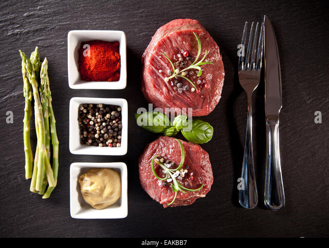 Pieces of red raw meat steaks with herbs, served on black stone surface. Shot from upper view. - Stock Image