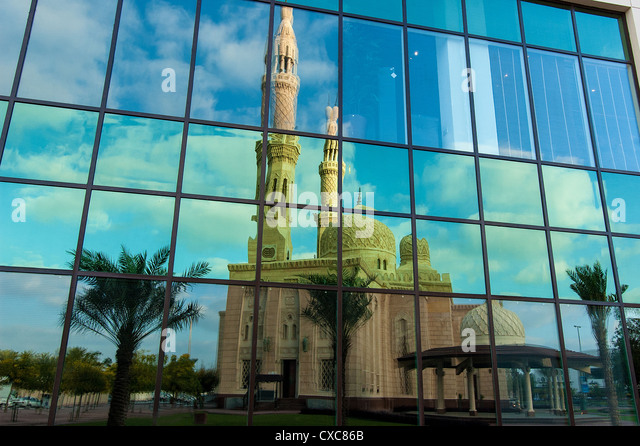 The Jumeirah Mosque, the largest mosque of Dubai, through its reflection on the windows of a skyscraper - Stock-Bilder