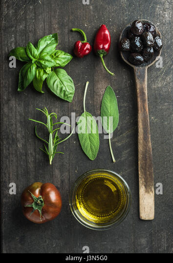Vegetables and herbs on dark rustic wooden background. Greek black olives, fresh green sage, rosemary, basil herbs, - Stock Image