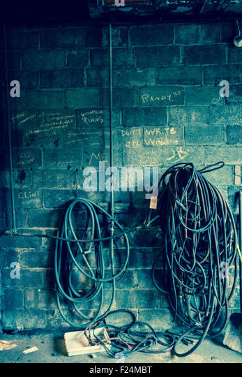 Twisted wires and hoses beneath chalk writing on a cement block wall, with a blue tone. - Stock Image