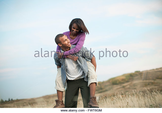 Man giving girlfriend a piggyback ride outdoors. - Stock Image