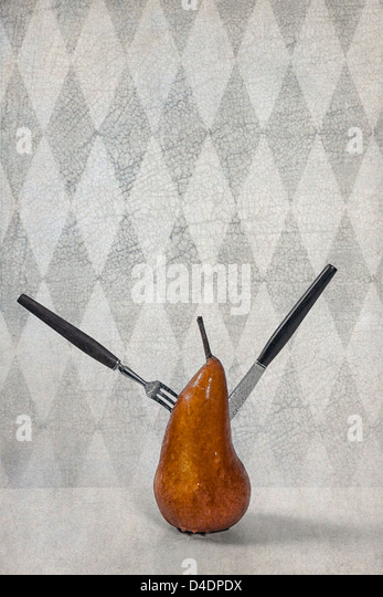 a pear, pierced with a fork and a knife - Stock Image