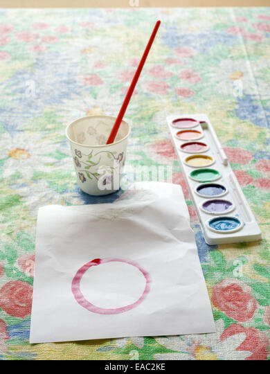 Child's Paint, Paint Brush and Paper on Table - Stock Image