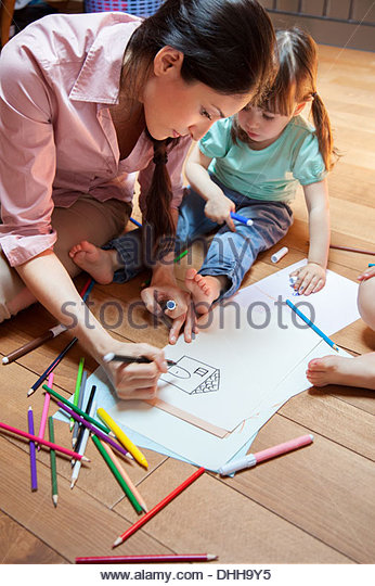 Mother and daughter drawing picture of house - Stock-Bilder