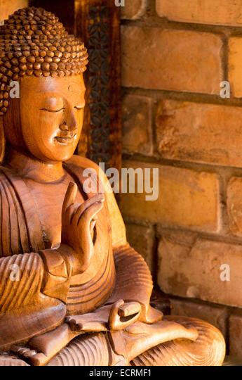Wooden buddha by brick wall - Stock Image