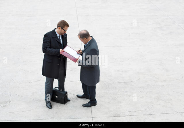 Two businessmen on square signing ducument - Stock Image