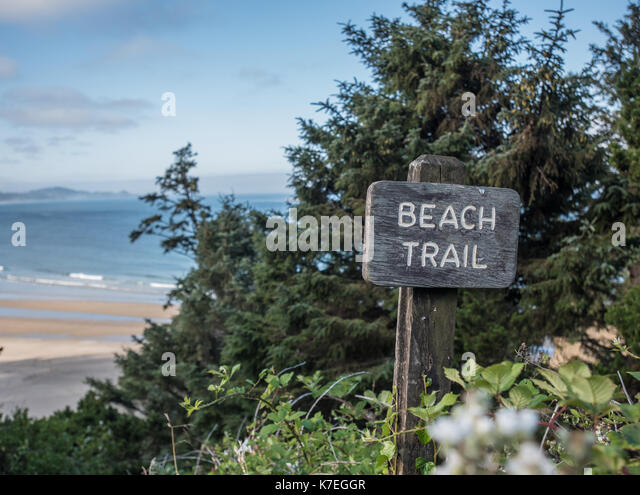 Beach Trail Sign Above Pacific Ocean with beach in background - Stock Image