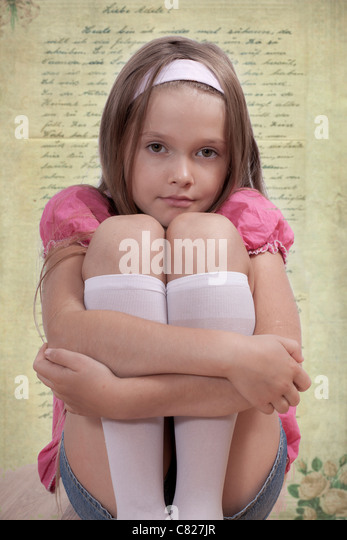 seated girl looks dreamily into the camera, with old letter as a background - Stock Image