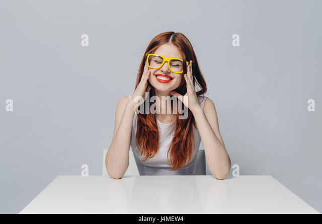 Laughing Caucasian woman sitting at table wearing yellow eyeglasses - Stock-Bilder