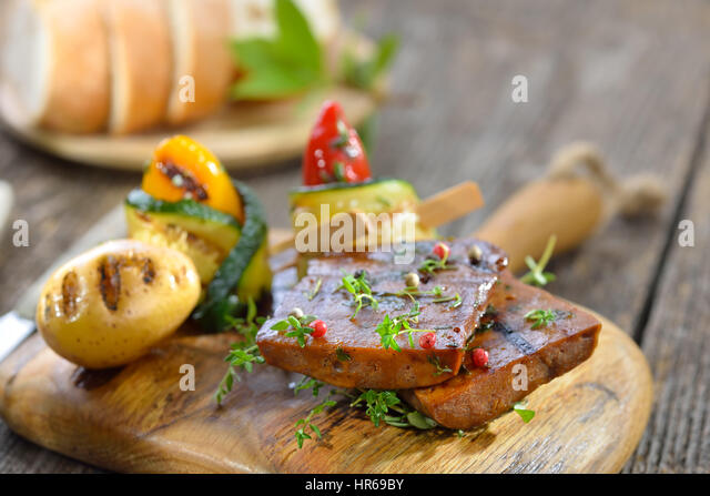 Vegetarian grill platter with vegan seitan slices, courgette rolls with peppers and grilled potato - Stock Image