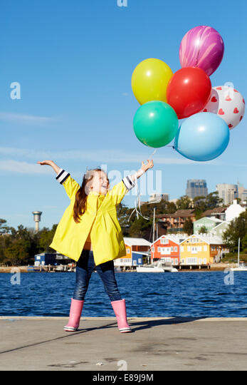 Girl in raincoat holding balloons - Stock-Bilder