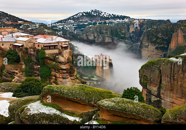 Meteora monasteries in fog. Varlaam monastery (left) and Roussanou monastery (center) are 2 of 6 still active monasteries - Stock Image