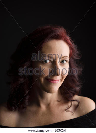 Close up portrait smiling woman with bare shoulders and red hair against black background - Stock Image