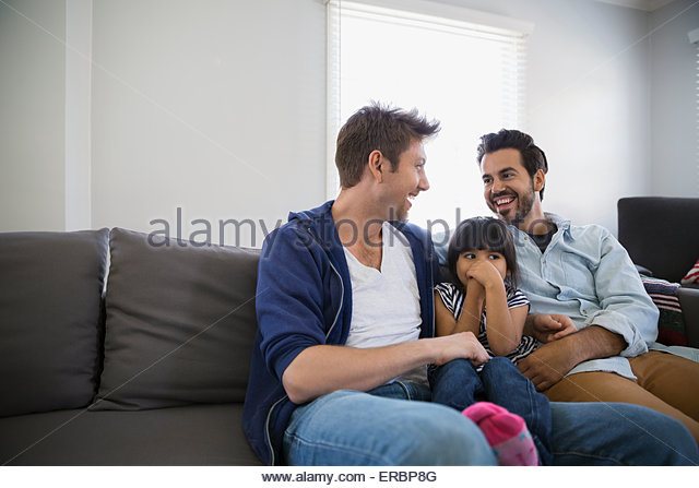 Affectionate homosexual couple and daughter on sofa - Stock Image