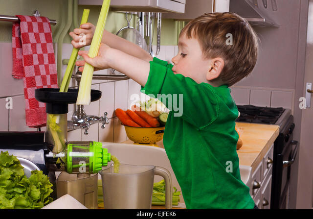 Little boy making green juice - Stock Image