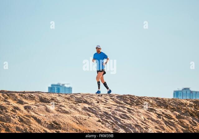 Low angle view of mid adult man running on sand dune, Dubai, United Arab Emirates - Stock Image