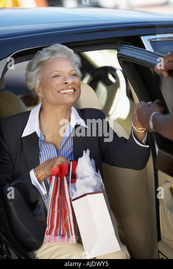 woman getting out car holding stock photos woman getting out car holding stock images alamy. Black Bedroom Furniture Sets. Home Design Ideas