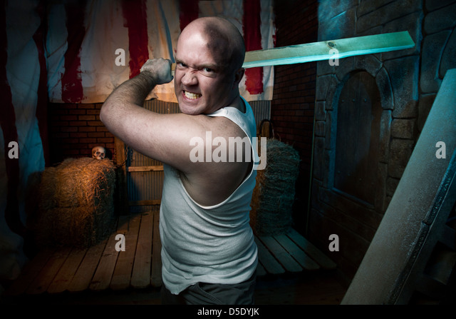 Man attacking with board in tented dark alley - Stock Image