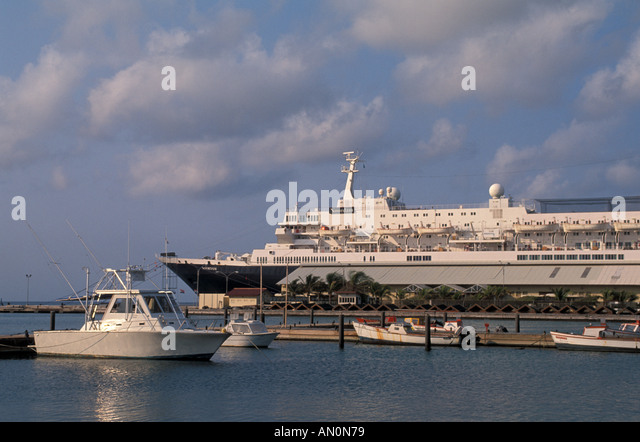 Cruise Ship docked in Oranjestad Aruba small local fishing boats in the foreground - Stock Image