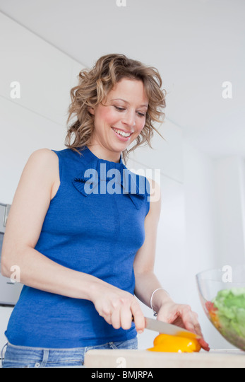 Woman cutting yellow bell pepper - Stock Image