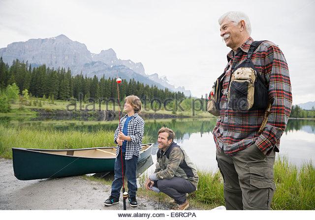 Three generations of men by still lake - Stock Image