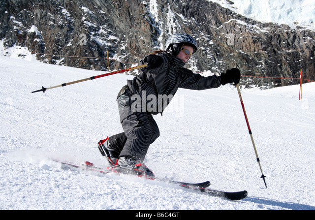 Nine year old girl skiing in Telemark style on the slopes of Saas Fee, Swiss, Europe - Stock Image