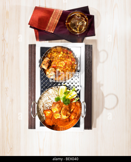 Indian food, a dish of chicken tikka masala served with lentils and bhajji. - Stock Image