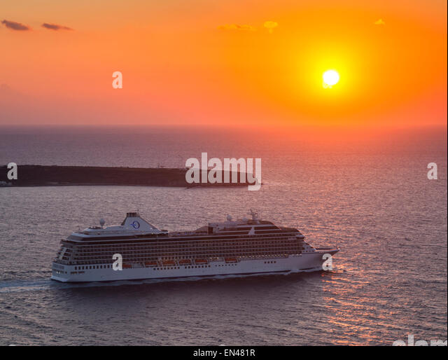 Cruise ship departing Santorini by the evening sunset headed for a new destination, Thera, Greece. - Stock-Bilder