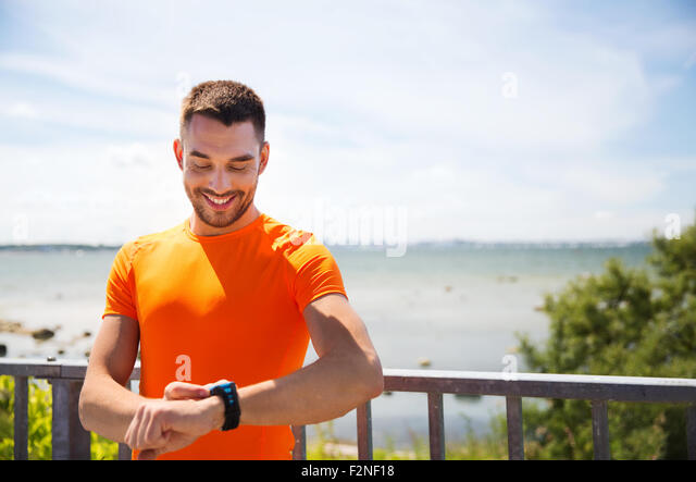 smiling young man with smart wristwatch at seaside - Stock Image