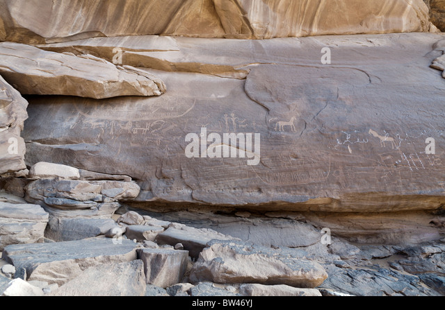 Petroglyph of large boat and various animals overlaid by modern painted graffiti, Wadi el-Barramiya, Eastern Desert, - Stock Image