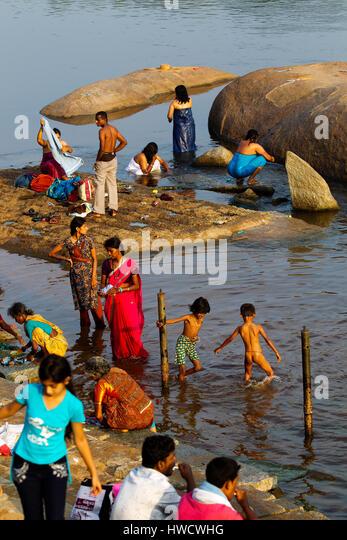 Indian people refreshing themselves on the waters of Tungabhadra river, Hampi, Karnataka, India - Stock-Bilder