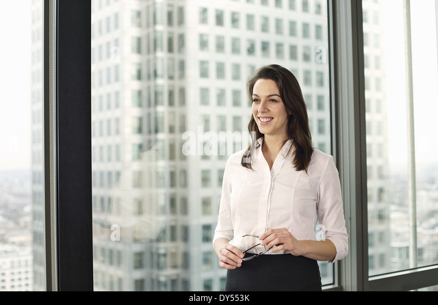 Portrait of young businesswoman in high rise office - Stock Image