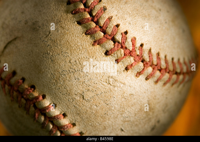 A scuffed and used baseball after hard use seen close up. - Stock Image