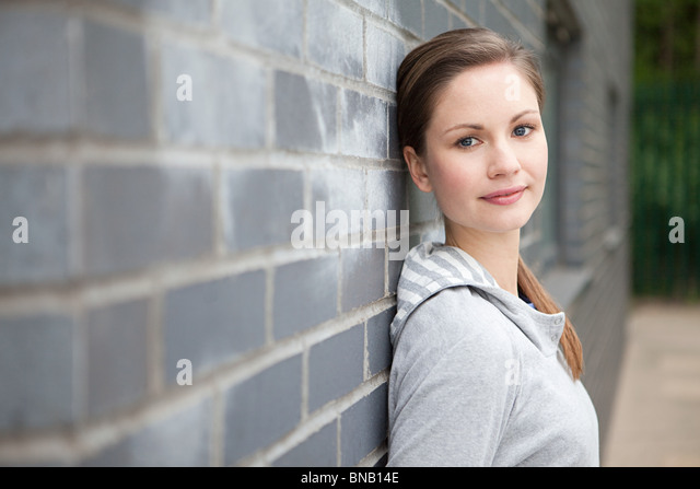 Young woman by wall - Stock Image