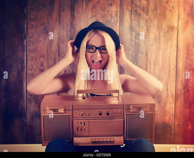 A blonde hipster girl with glasses is listening to a vintage gold boombox radio with a speaker for a music entertainment - Stock Image