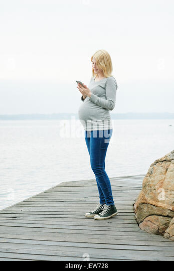 Pregnant woman on jetty using cell phone - Stock Image