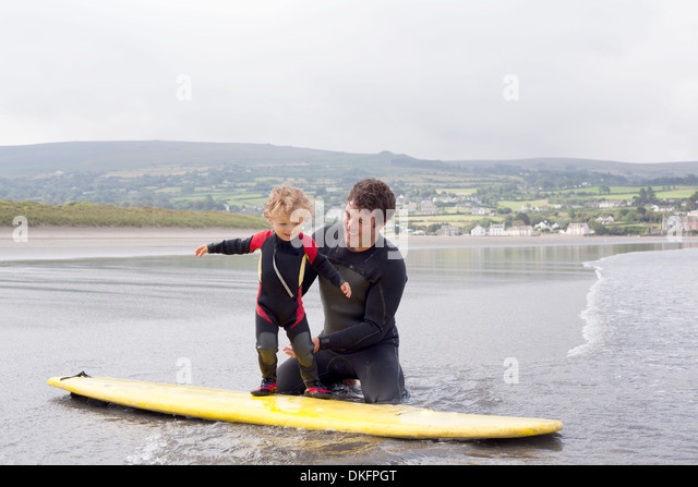 Father teaching son how to surf - Stock Image