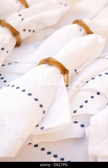 Close up full frame of napkins with diamond pattern arranged in bamboo napkin rings - Stock Image