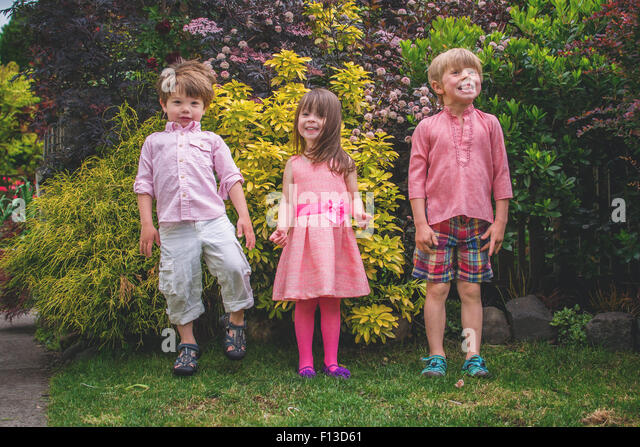 Three children standing in a row - Stock Image