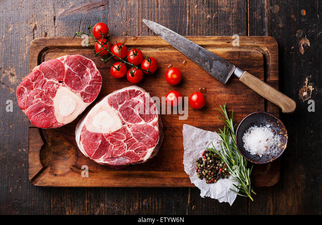 Raw fresh cross cut veal shank and seasonings for making Osso Buco on wooden cutting board - Stock Image