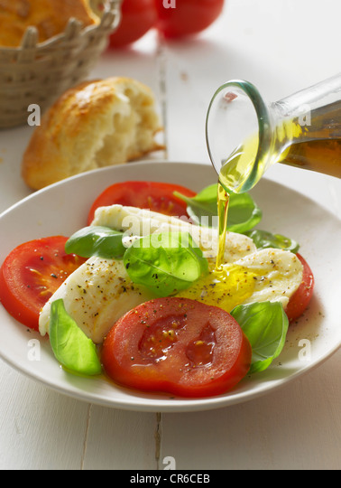 Olive oil pouring on caprese salad in plate, close up - Stock-Bilder