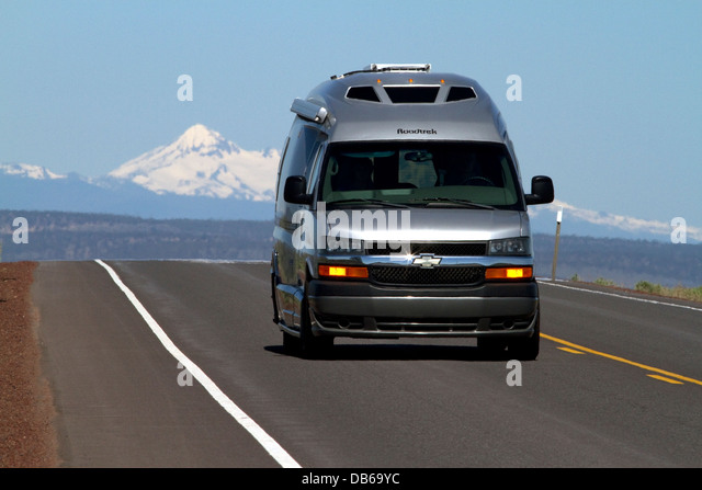 Automobile traveling on U.S. Route 20 east of Bend, Oregon, USA. - Stock Image