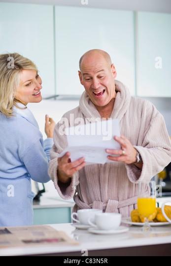 Surprised man reading mail - Stock Image